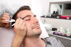 Man eyebrows with tweezers Royalty Free Stock Photography