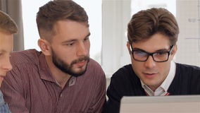 Man in eyeglasses explaines something on laptop to his male colleagues stock video footage