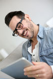Man with eyeglasses looking at tablet Stock Images