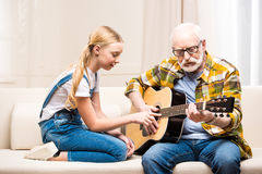 Man in eyeglasses teaching cute little granddaughter playing acoustic guitar. Senior men in eyeglasses teaching cute little granddaughter playing acoustic guitar Stock Photography