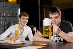 Man eyeing a large tankard of beer in anticipation. As he sits with a friend enjoying an evening out together at the pub Stock Image