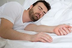 Man with eyes closed in bed sleep Stock Image