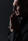 Man with eyes closed holding rosary and praying. Over black background Stock Photography