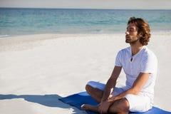 Man with eyes closed meditating at beach. Man with eyes closed meditating while sitting on exercise mat at beach Royalty Free Stock Photography