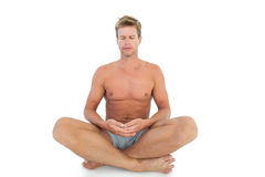 Man with eyes closed meditating on the floor. On white background royalty free stock image