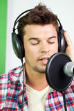 Man With Eyes Closed Singing In Recording Studio. Closeup of young man with eyes closed singing in recording studio Royalty Free Stock Photography