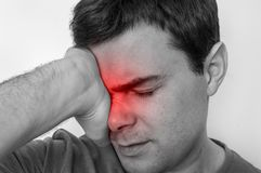 Man with eyes pain is holding his aching eye. Black and white photo Royalty Free Stock Images