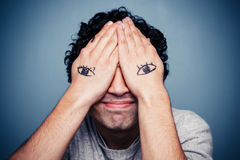 Man with eyes painted on his hands. Young man with eyes painted on his hands is covering his face Stock Photo