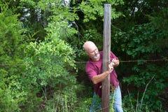 Man för äldre vuxen människa som reparerar staketet Arkivbild