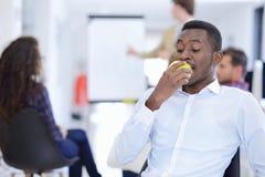 Man för affär för Closeupstående allvarlig, avtalstillverkare som äter det gröna äpplet arkivbild