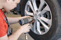 Man för auto mekaniker med det ändrande gummihjulet för elektrisk skruvmejsel utanför service för utbyte för bunkebilelevator lyf arkivfoton