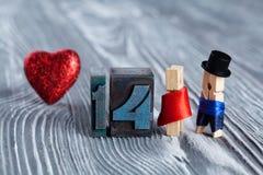 man för begreppskyssförälskelse till kvinnan red steg 14 Februari klädnypor Arkivbilder