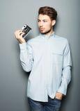 Man för Hipstermodefotograf som rymmer den retro kameran royaltyfria foton
