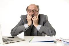 Man för mogen affär med flinten på hans funktionsdugliga stressat för 60-tal och frustrerat på skrivbordet för bärbar dator för k royaltyfri fotografi