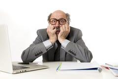 Man för mogen affär med flinten på hans funktionsdugliga stressat för 60-tal och frustrerat på skrivbordet för bärbar dator för k arkivfoton