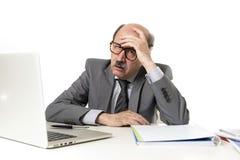 Man för mogen affär med flinten på hans funktionsdugliga stressat för 60-tal och frustrerat på skrivbordet för bärbar dator för k royaltyfria foton