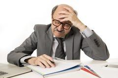 Man för mogen affär med flinten på hans funktionsdugliga stressat för 60-tal och frustrerat på skrivbordet för bärbar dator för k arkivbild
