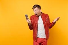 Man för skrikig ilsken nedgång för ståendemode ung i röd t-skjorta för läderomslag genom att använda mobiltelefonen som isoleras  royaltyfria foton