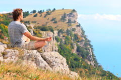 Man för yogameditationen för handelsresanden avslappnande sammanträde på stenar med Rocky Mountains och blå himmel på bakgrund Royaltyfria Bilder