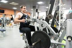 Man förlovat i fysisk övning i idrottshallen Royaltyfri Bild