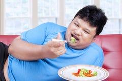 Man försöket att banta, genom att äta grönsak 1 royaltyfria bilder