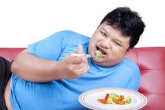 Man försöket att banta, genom att äta grönsak 2 royaltyfri foto