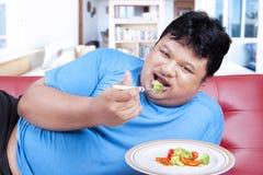 Man försöket att banta, genom att äta grönsak 3 Royaltyfri Foto