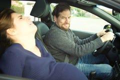Man förskräckt av frun som ger födelse i bil royaltyfria foton