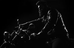 Man face. Courage. Man with beard, biker in leather jacket sitting on motor bike in darkness, black background. Night Royalty Free Stock Images