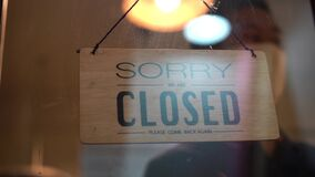 Man in face mask closing store during covid 19 lockdown, closing work, shutting business due to bankruptcy.