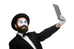 Man with a face mime looks in the laptop as mirror Stock Image