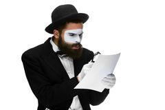 Man with a face mime reading through magnifying Stock Photography