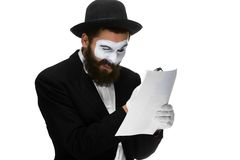 Man with a face mime reading through magnifying Stock Images