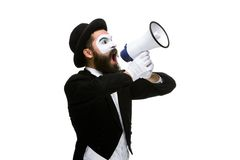 Man with a face mime screaming into megaphone. Man  with a face mime screaming into a megaphone, isolated on white background. concept of effective communication Royalty Free Stock Image