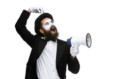 Man with a face mime screaming into megaphone. Man  with a face mime screaming into a megaphone, isolated on white background. concept of effective communication Stock Image