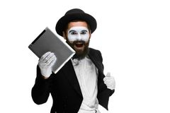 Man with a face mime working on laptop Stock Photography
