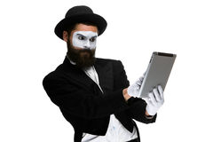 Man with a face mime working on  laptop Stock Image