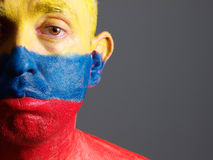Man face painted with colombian flag, sad expression. Stock Image