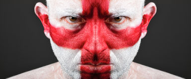Man face painted with flag of England. Man with his face painted with the flag of England.  The man is serious and photographic composition leaves only half of Stock Images