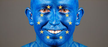 Man face painted with the flag of European Union. Man with his face painted with the flag of European Union. The man is smiling and photographic composition Stock Image