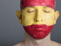 Man face painted flag Spain, closed eyes. Royalty Free Stock Photo