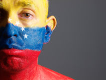 Man face painted with venezuelan flag, sad expression. Royalty Free Stock Photo
