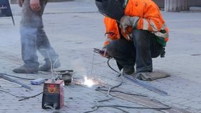 A man with face protection welds metal parts. The welder is working on the street.  stock video