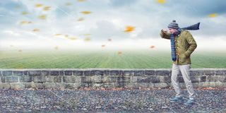 Man faces head wind. Panoramic image of a man with a cap and scarf walking on a sidewalk against a strong wind. Cloudy weather with flying leafs Stock Image