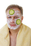 Man with facial mask and cucumber Stock Photo