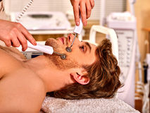 Man facial massage beauty salon. Electric stimulation man skin care . Royalty Free Stock Images
