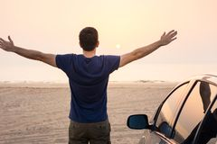 Man facing beach sunset by the car. Summer vacation time stock photo