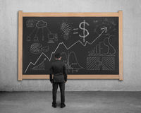 Man facing business concept doodles on blackboard Stock Photography