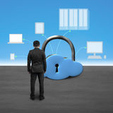Man facing cloud shape lock with computing devices. Blue sky background royalty free stock photo