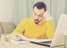 Man facing difficulty. Young male student having complicated issue at online courses at home Royalty Free Stock Photos